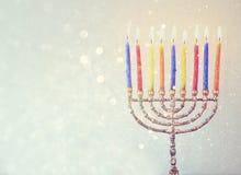 Low key image of jewish holiday Hanukkah background with menorah Burning candles over glitter background Stock Photos