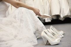 Low section of woman sitting with variety of footwear in bridal boutique Royalty Free Stock Image