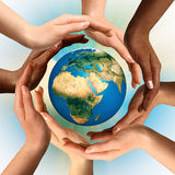 Mãos Multiracial que cercam o globo da terra Imagens de Stock