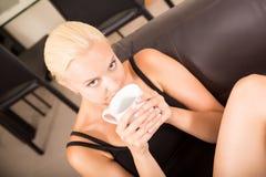 Mädchen, das auf einem Sofa trinkt einen Tasse Kaffee sich entspannt Stockfotos