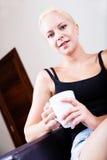 Mädchen, das auf einem Sofa trinkt einen Tasse Kaffee sich entspannt Stockbilder