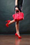 Mädchen in den schwarzes kurzes Kleiderroten ährentragenden Schuhen hält Handtasche Lizenzfreie Stockfotos