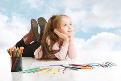 Mädchenträumen, nach Zeichnungsidee suchend. Lächelnder Kinderlügenhimmel Stockfotos
