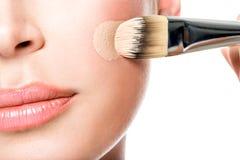 Makeup artist applying liquid tonal foundation  on the face Royalty Free Stock Image