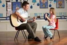 Male Teacher Playing Guitar With Pupil In Classroo Royalty Free Stock Photography