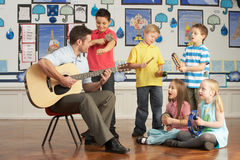 Male Teacher Playing Guitar With Pupils Royalty Free Stock Photo