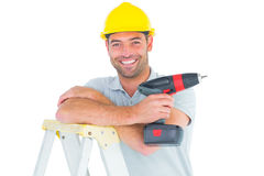 Male technician holding power drill on ladder Royalty Free Stock Image