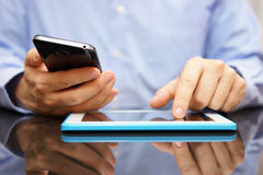Male is using smart mobile phone and tablet computer at the same Royalty Free Stock Photography
