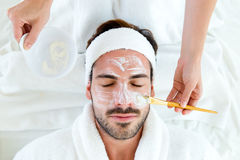 Man with clay facial mask in beauty spa. Royalty Free Stock Images