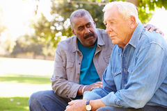Man Comforting Unhappy Senior Friend Outdoors Royalty Free Stock Photography