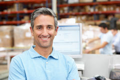 Man At Computer Terminal In Distribution Warehouse Stock Image