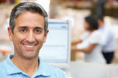 Man At Computer Terminal In Distribution Warehouse Stock Photos