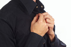 Man fastened the buttons of collar on the black shirt Stock Photo