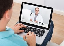 Man having video chat with doctor Stock Photography