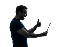 Man holding digital tablet  thumb up satisfied  silhouette Royalty Free Stock Images