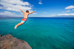 Man jumping off cliff into the ocean Stock Photography
