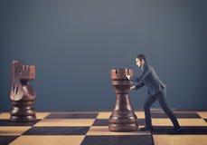 Man pushing chess pieces Stock Image