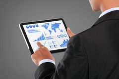 Man pushing on a touch screen tablet of infographics Stock Photos