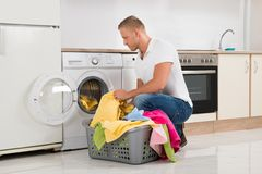 Man Putting Dirty Clothes Into The Washing Machine Royalty Free Stock Image