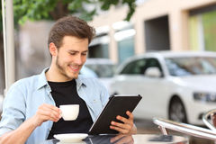 Man reading an ebook or tablet in a coffee shop Stock Photo