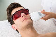 Man Receiving Laser Hair Removal Treatment Stock Photo