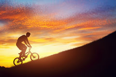 Man riding a bmx bike uphill against sunset sky. Strength, challenge. Stock Photography