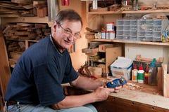 Man sitting at workbench in workshop Stock Photo