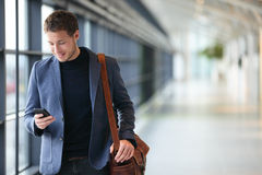 Man on smart phone - young business man in airport Royalty Free Stock Image