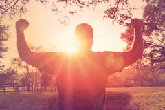 Man standing with arms raised in victory gesture Royalty Free Stock Photo