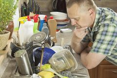 Man washing dirty dishes in the kitchen sink. Royalty Free Stock Image