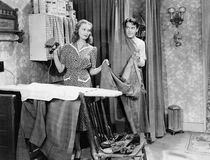 Man and woman standing in a kitchen while she is ironing his pants and he is behind a curtain Stock Image