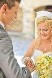 Mariée donnant la boucle au marié Photo stock