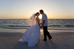 Mariage de plage de baiser de coucher du soleil de couples de mariée et de marié Images libres de droits