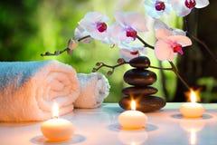 Massaggi la stazione termale della composizione con le candele, le orchidee e le pietre nere in giardino Immagini Stock Libere da Diritti