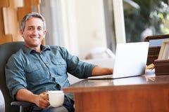 Mature Hispanic Man Using Laptop On Desk At Home Royalty Free Stock Images