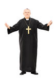 Mature reverend in black mantle with open hands Royalty Free Stock Photography