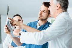 Medical team examining patient's x-ray Stock Photos