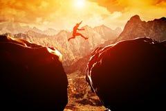 Mens die over afgrond tussen twee bergen springen Stock Afbeeldingen