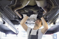 Mid adult automobile mechanic repairing car in workshop Royalty Free Stock Images