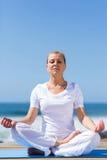 Mid age woman meditating Stock Image