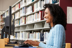 Mid age woman working on computer in library Stock Photos