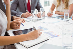 Mid section of executives writing notes in board room meeting Stock Photo