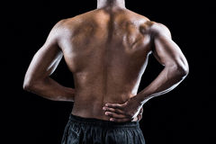Mid section of muscular athlete suffering through back pain Stock Photos