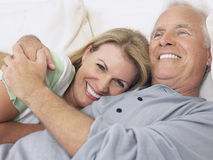 Middle Aged Couple Embracing In Bed Stock Photos