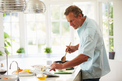 Middle Aged Man Following Recipe On Digital Tablet Royalty Free Stock Photography