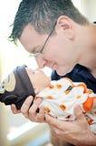 Middle aged man holding newborn Stock Photos