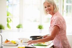 Middle Aged Woman Following Recipe On Digital Tabl Stock Photos