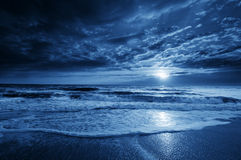 Midnight Blue Coastal Moonrise With Dramatic Sky and Rolling Waves Royalty Free Stock Photography