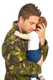 Military father embracing his baby son Stock Photos