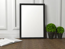 Mockup of blank frame poster and green flower on the floor Stock Image